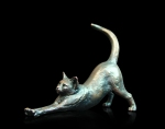 Bronze sculpture of a cat stretching