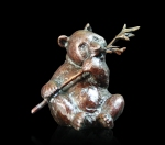 Bronze sculpture of a sitting baby panda feeding on bamboo