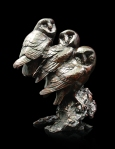 Bronze sculpture of three barn owls perched on a branch