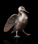 Bronze sculpture of a Mallard duck on the ground stretching it's wings
